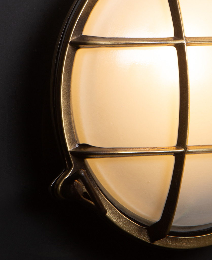 chris aged brass Bulkhead LED Light close up against black wall