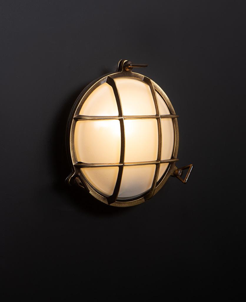chris aged brass Bulkhead LED light with lit bulb on black wall