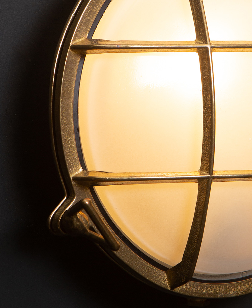 chris brass Bulkhead LED light with lit close up against black wall
