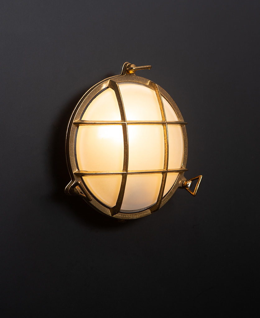 chris brass Bulkhead LED Light with lit bulb on black wall