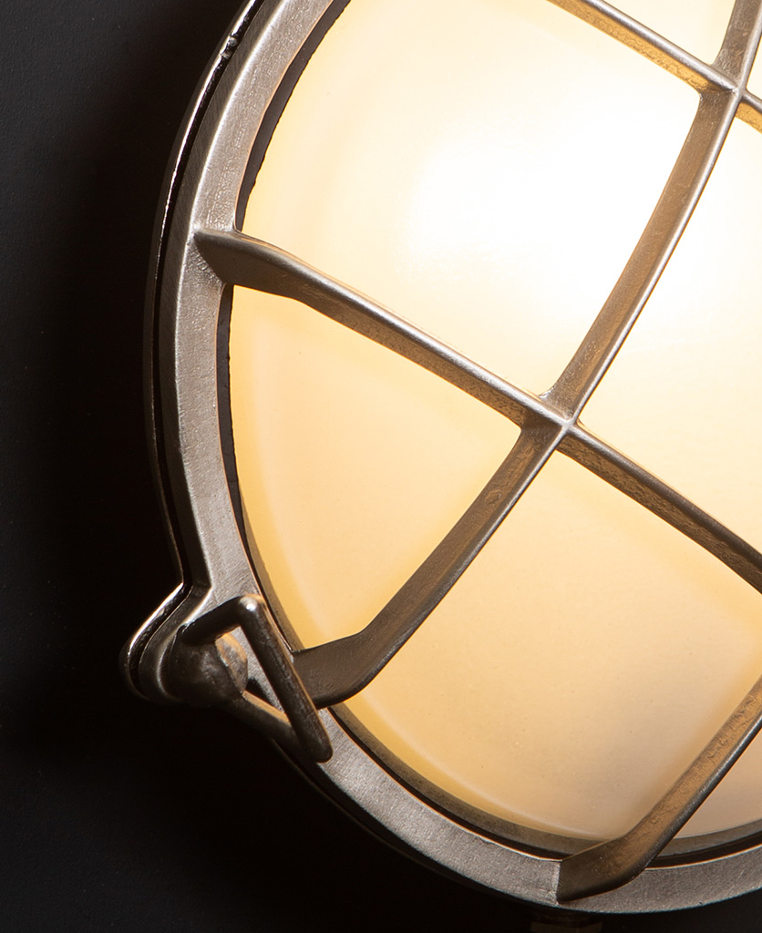 chris silver bulkhead LED Light close up against black wall