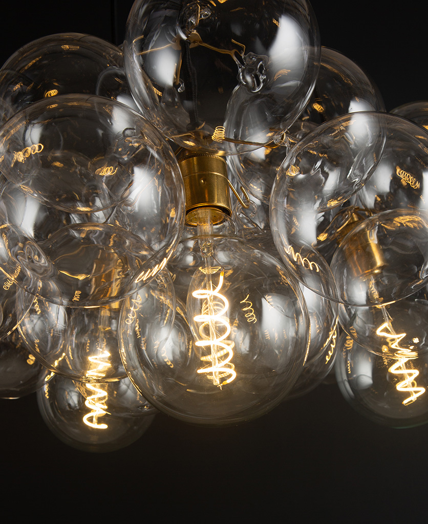closeup of gold bubble glass chandelier with gold bulb holders and spiral filament light bulb against a black wall