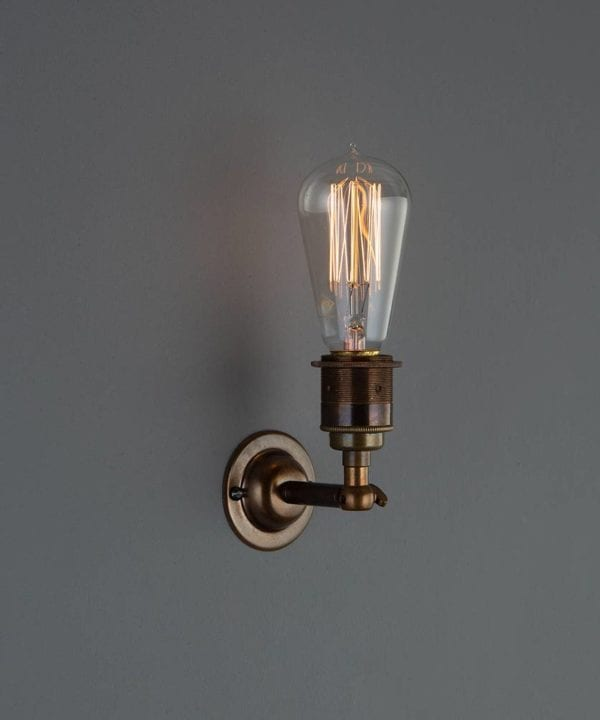 manston wall light brewer's brass with lit vintage light bulb against grey wall