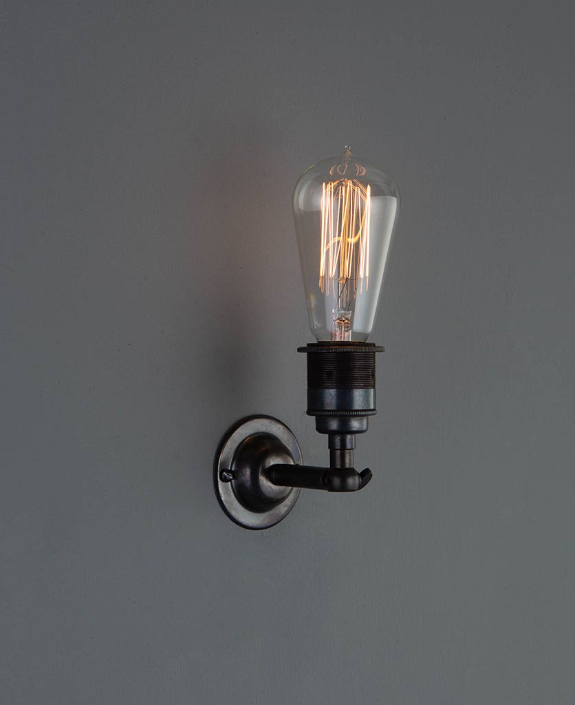 manston wall light antique brass with lit vintage light bulb against grey wall