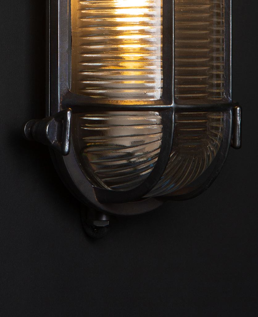 closeup of Steve pewter caged bulkhead light with lit bulb against black background