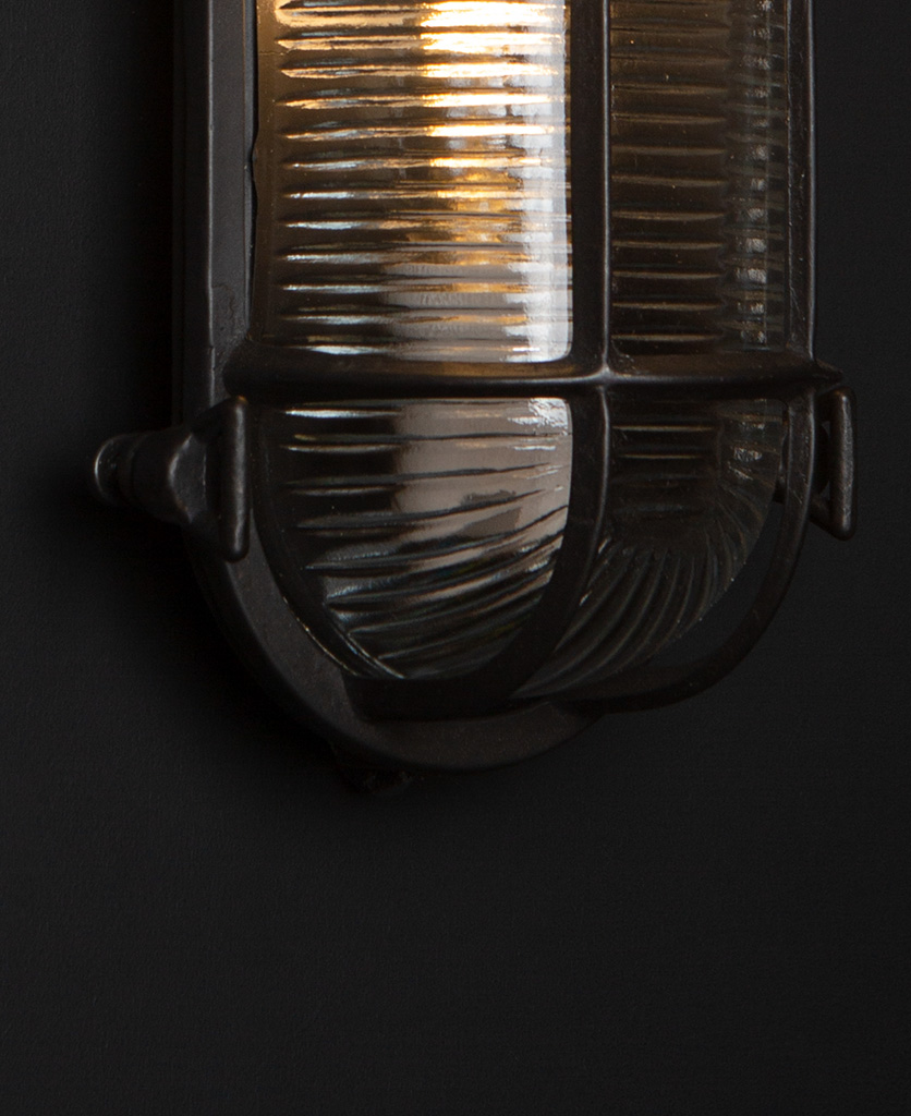 pewter steve bulkhead with wingnuts on black background with bulb close up