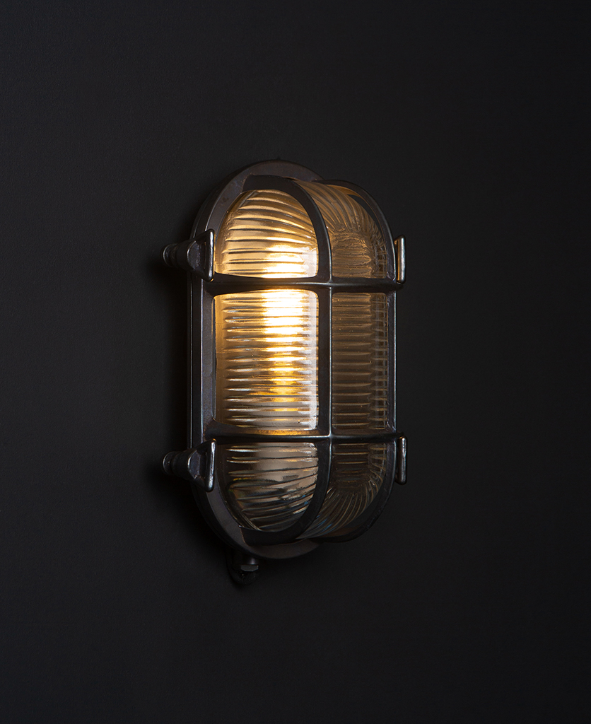 steve pewter bulkhead outdoor lights with lit bulb against black background