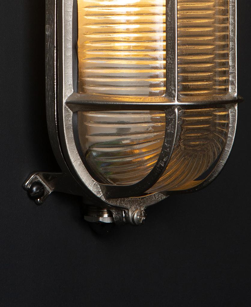 closeup of silver dave bulkhead light against black background