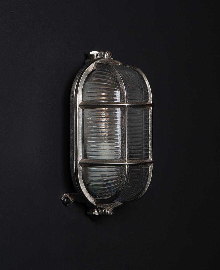 unlit silver dave outdoor bulkhead light on black background