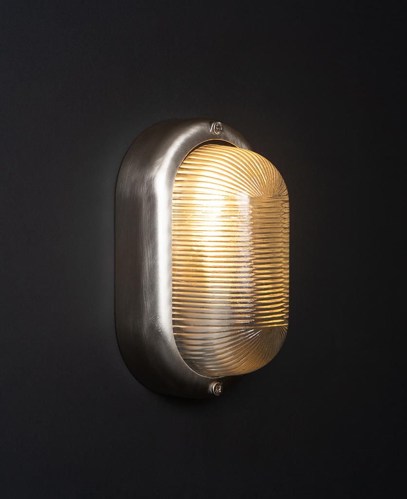 lit mike silver external led bulkhead light against black background