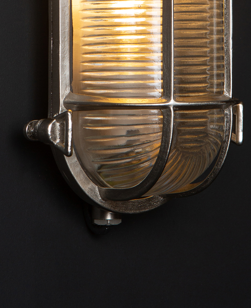 closeup of steve silver bulkhead outdoor lights with lit bulb against black background