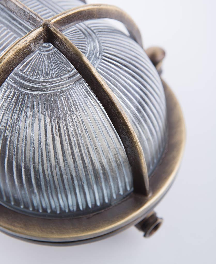 closeup of big steve aged brass bulkhead light against white background