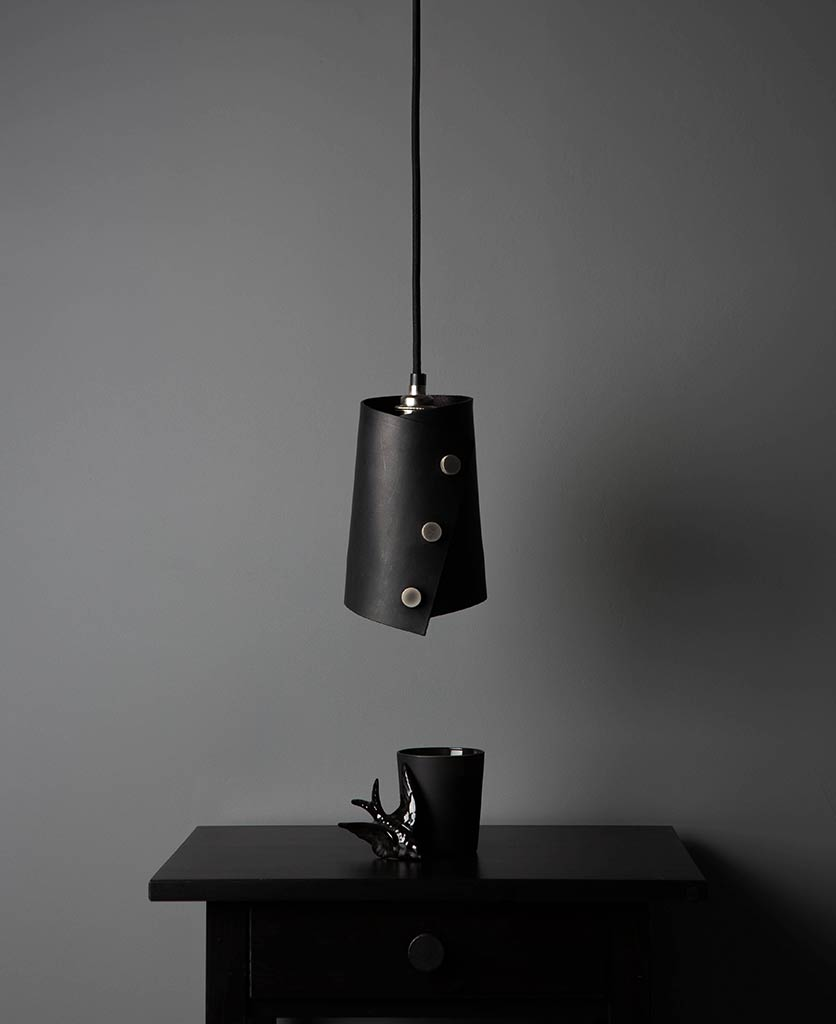 leather finish cuff pendant with black leather shade secured with knurled silver knobs, black fabric cable against dark grey background lifestyle