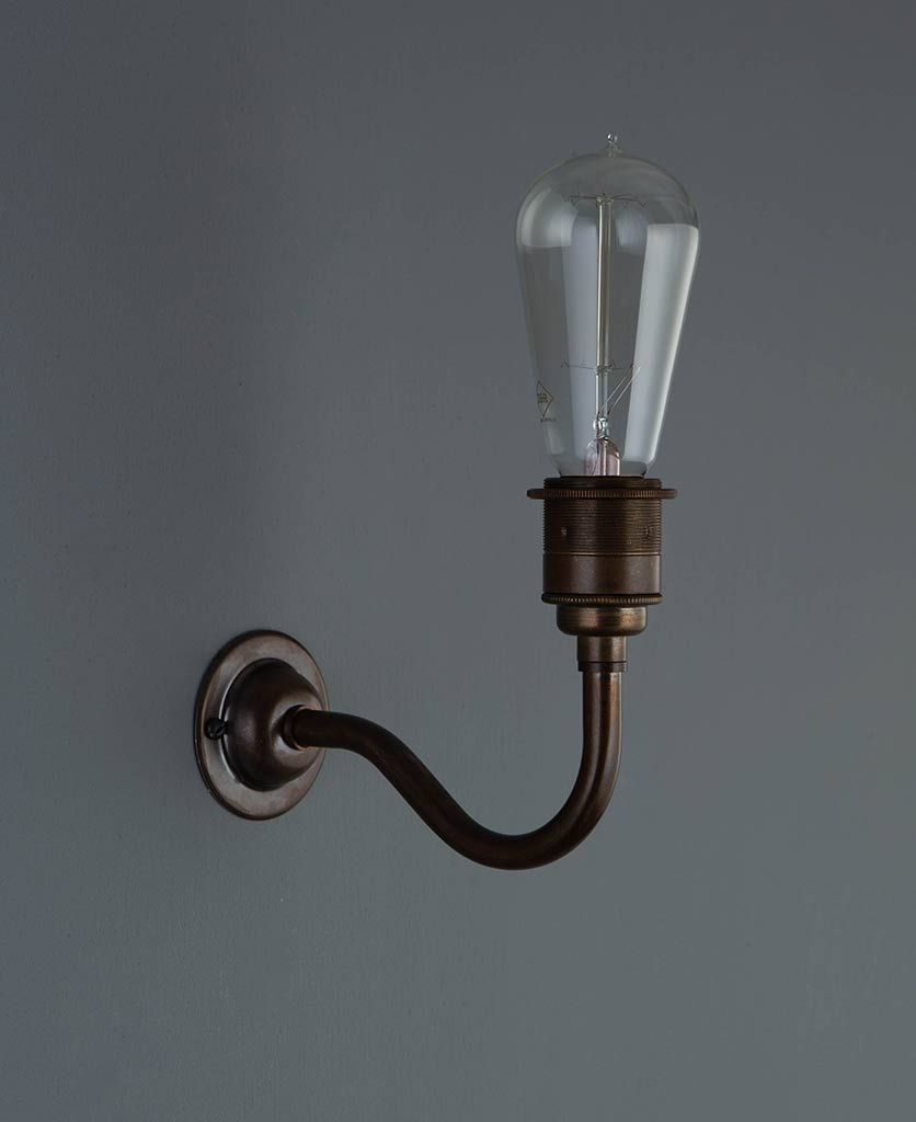bramley brewer's brass wall sconce with unlit filament bulb against grey wall