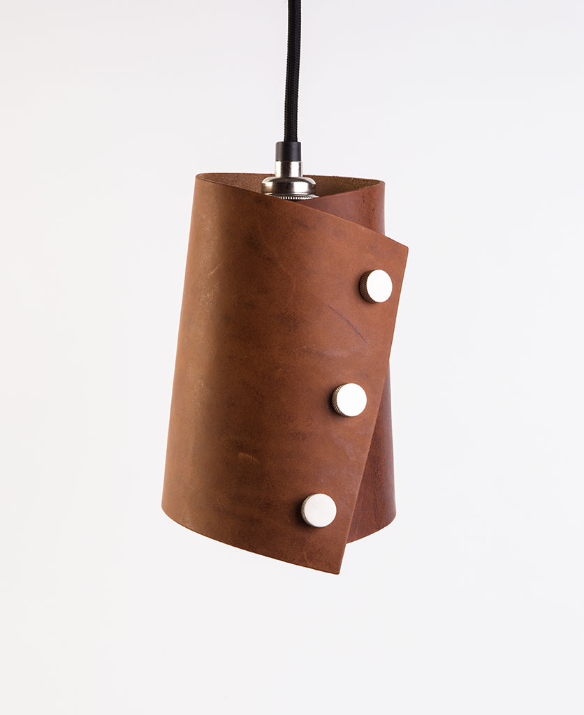 leather cuff pendant with dark tan leather shade secured with knurled silver knobs, black fabric cable against white background