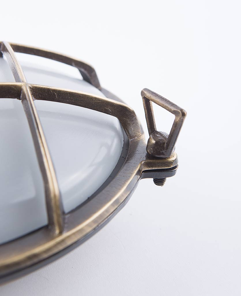 closeup of chris aged brass bulkhead light against whiote background