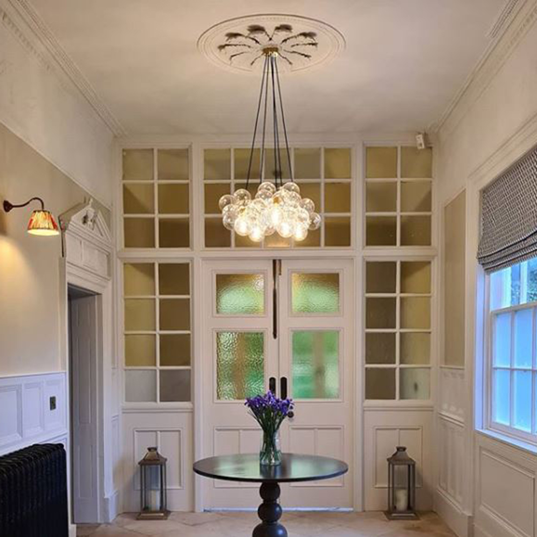 medium bubble chandelier suspended above a black table in a light grey and white interior