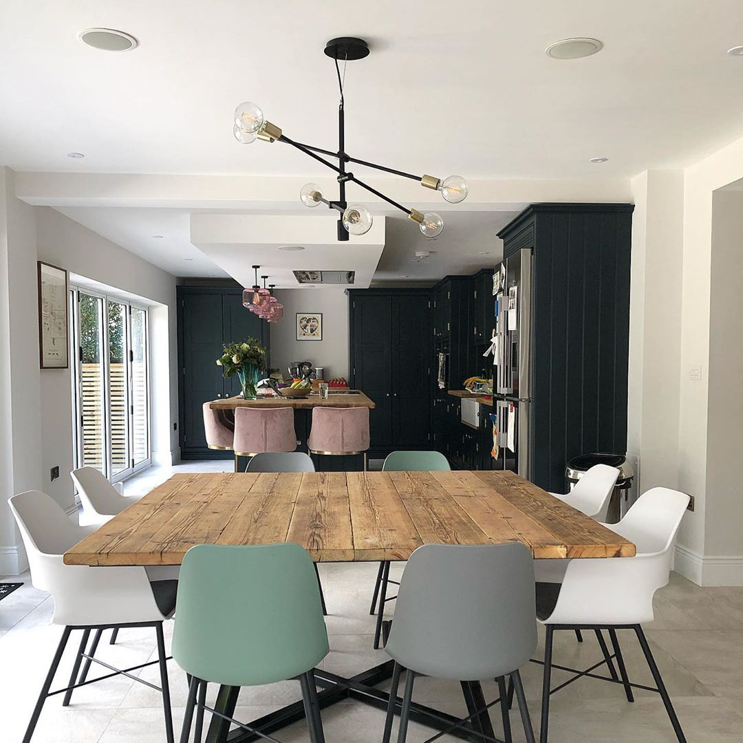Trikonasana black multi-arm light suspended over a wooden dining table in a black and white kitchen