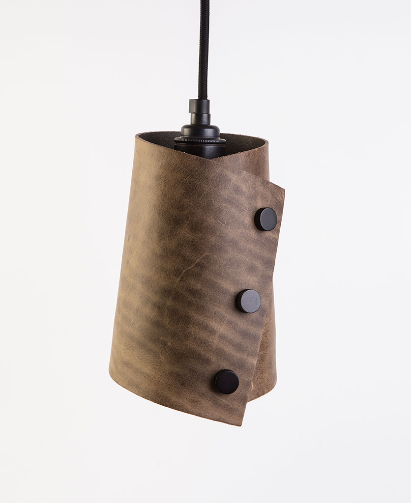 leather cuff pendant with light tan leather shade secured with knurled antique black knobs, black fabric cable against white background