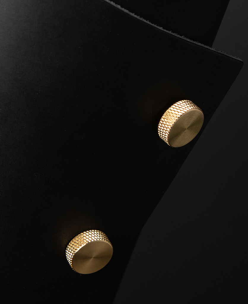 Black and Brass Leather Cuff Lamp Close Up against black background