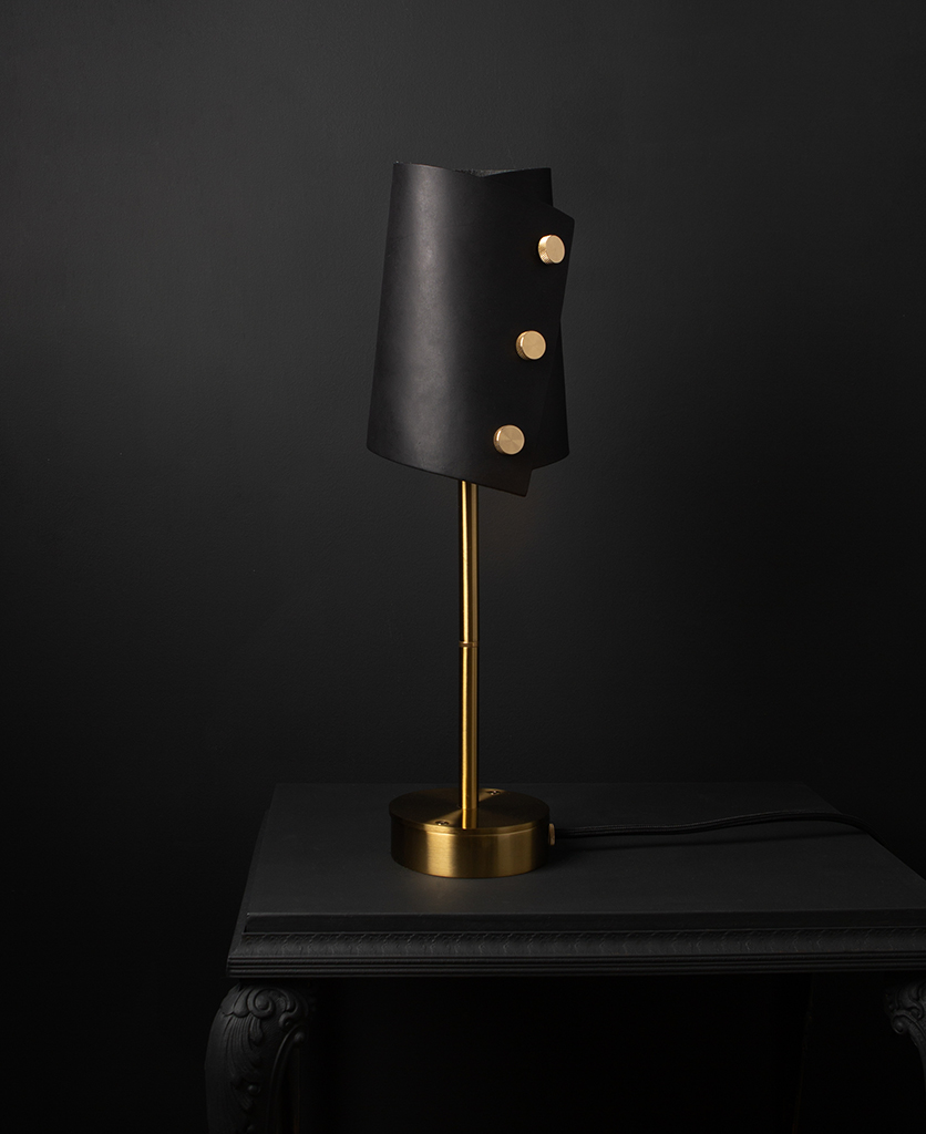 Leather desk lamp with black leather shade and brass base against black background