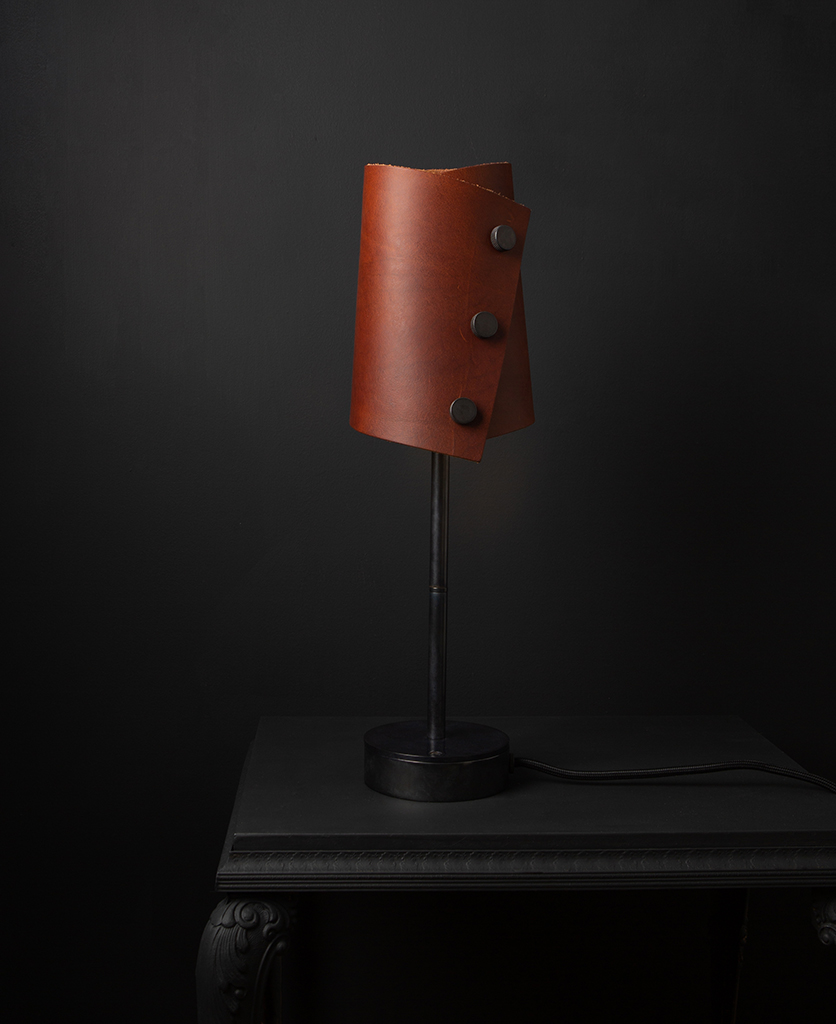 Leather table lamp with brown leather shade and antique black base against black background