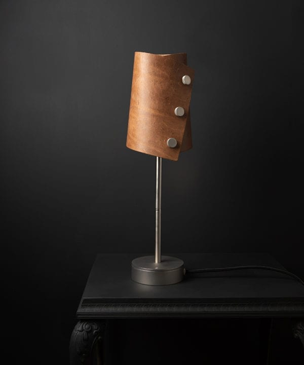 Leather lamp with tan leather shade and silver base against black background