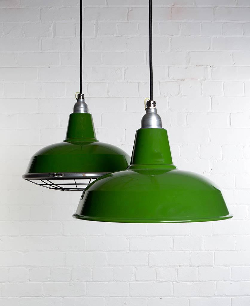 two green burley enamel pendant lights suspended from black fabric cable against painted white brick wall