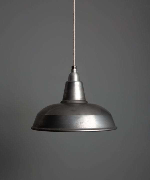 burley raw steel pendant light suspended from linen fabric cable against a dark grey wall
