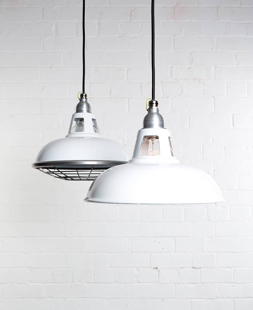 two white farsley enamel pendant lights suspended from black fabric cable against painted white brick wall