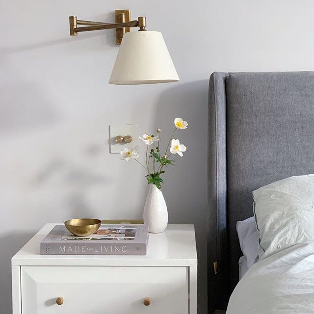 white double dimmer switch on white wall in a bedroom with white walls and grey bed