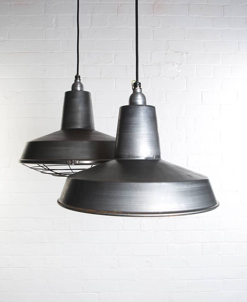 two raw steel linton enamel pendant lights suspended from black fabric cable against painted white brick wall