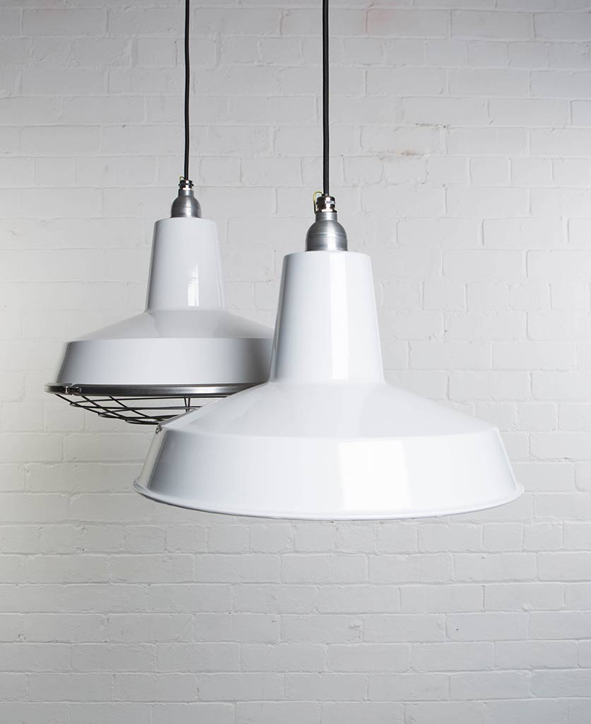 two white linton enamel pendant lights suspended from black fabric cable against painted white brick wall