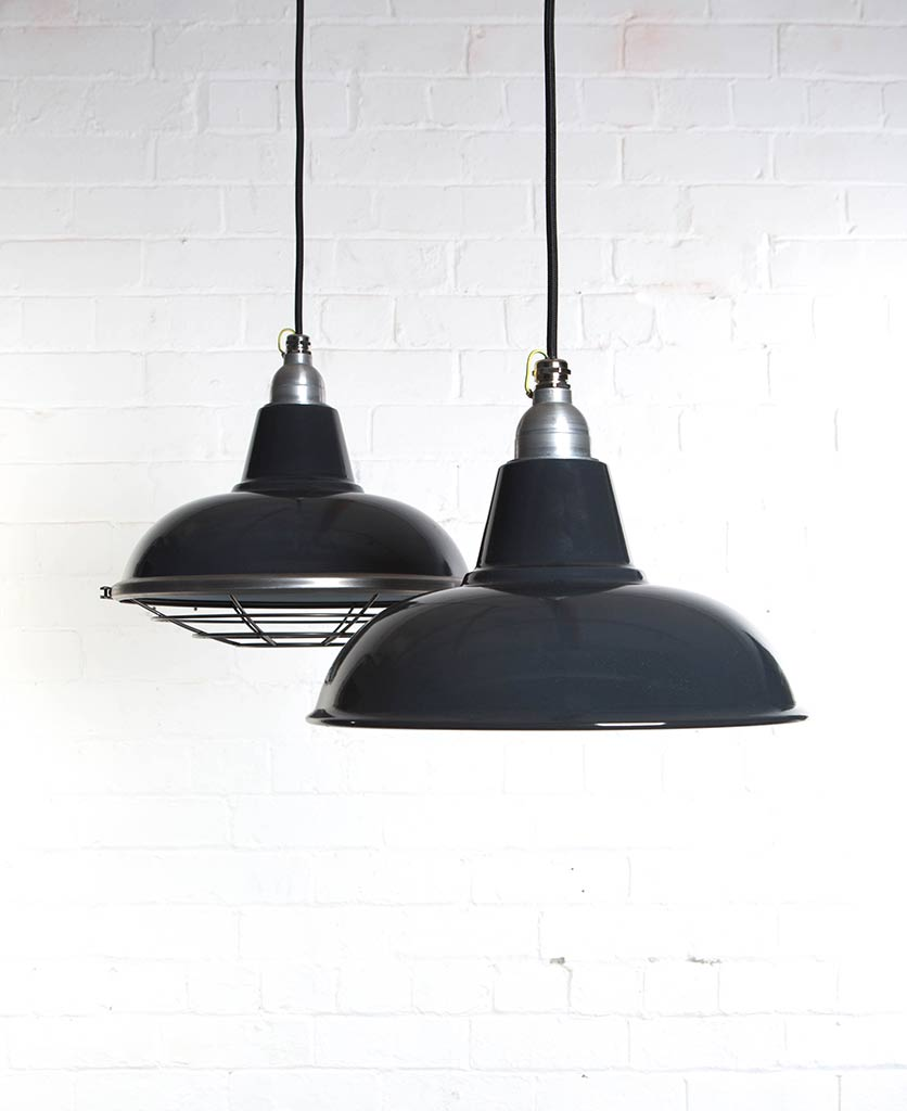 morley grey industrial lighting suspended from black fabric cable against white brick wall