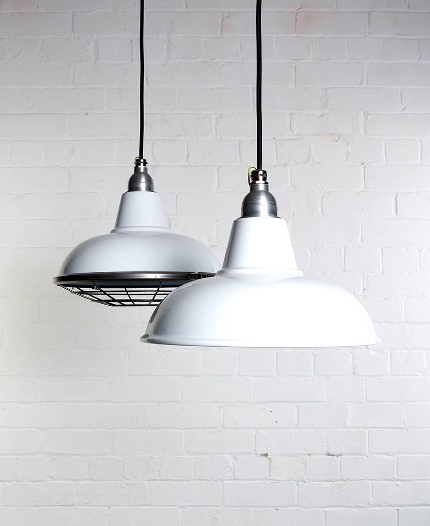 morley white industrial lighting suspended from black fabric cable against white brick wall