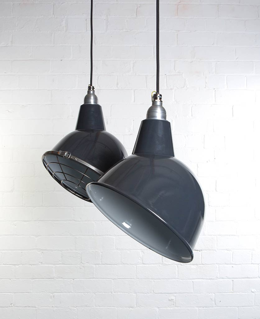 two grey oulton enamel pendant lights suspended from black fabric cable against painted white brick wall