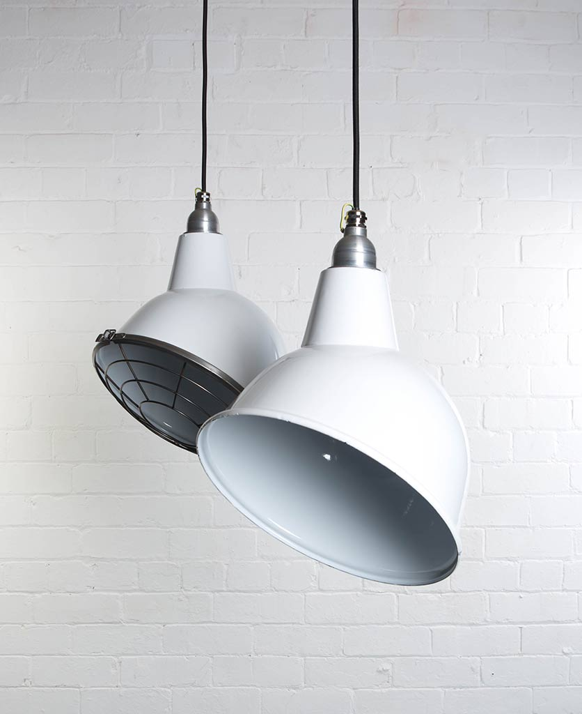 two white oulton enamel pendant lights suspended from black fabric cable against painted white brick wall