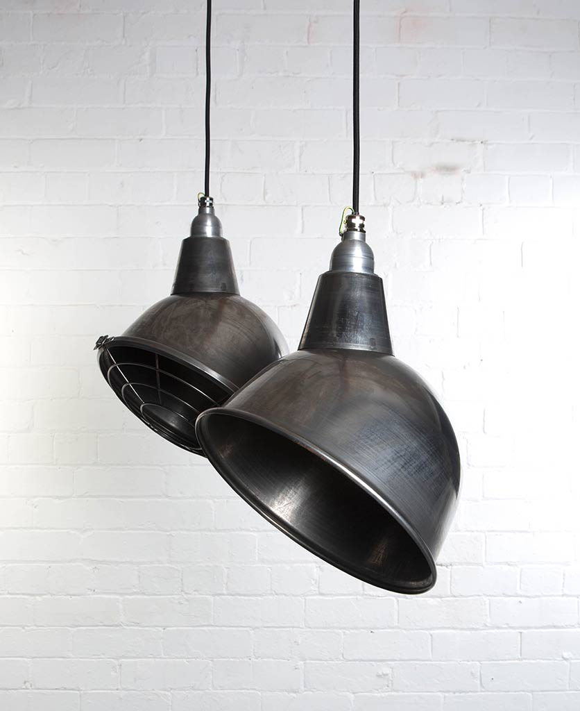 two raw steel oulton enamel pendant lights suspended from black fabric cable against painted white brick wall