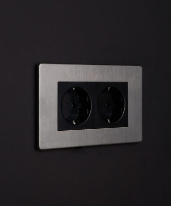 silver and black double schuko socket against black background