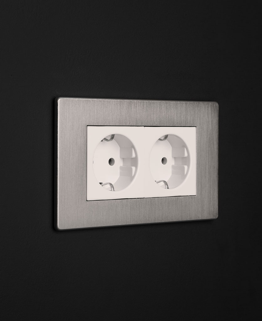 silver and white double schuko socket against black background