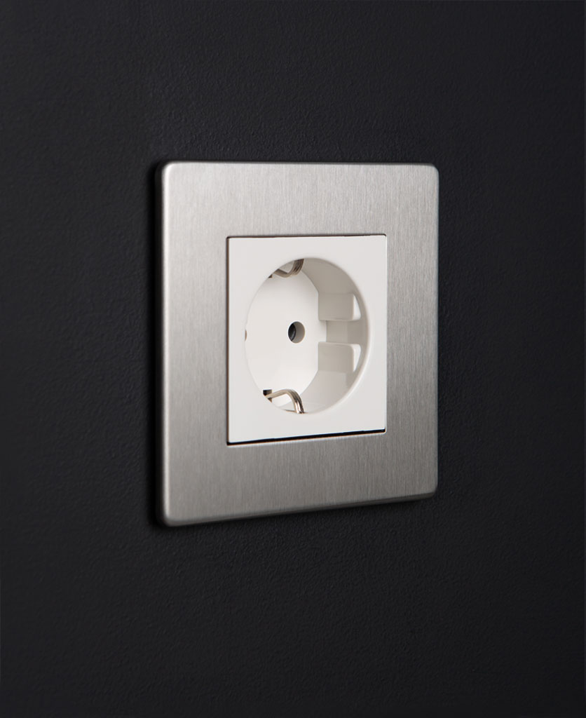 silver and white single schuko socket against black background