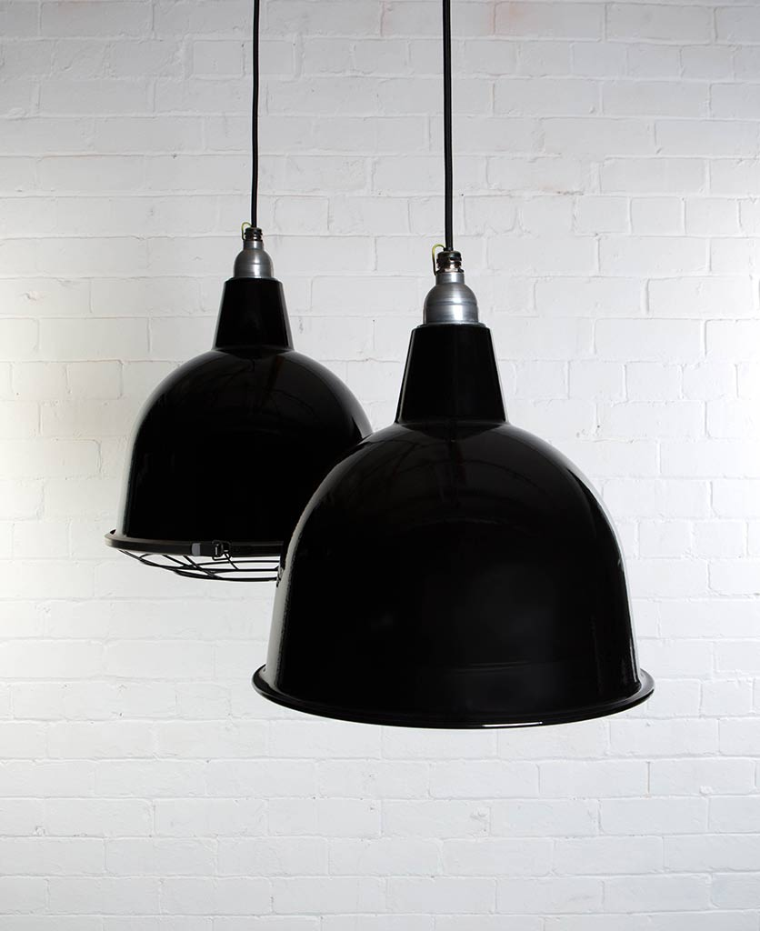 two black stourton enamel pendant lights suspended from black fabric cable against painted white brick wall