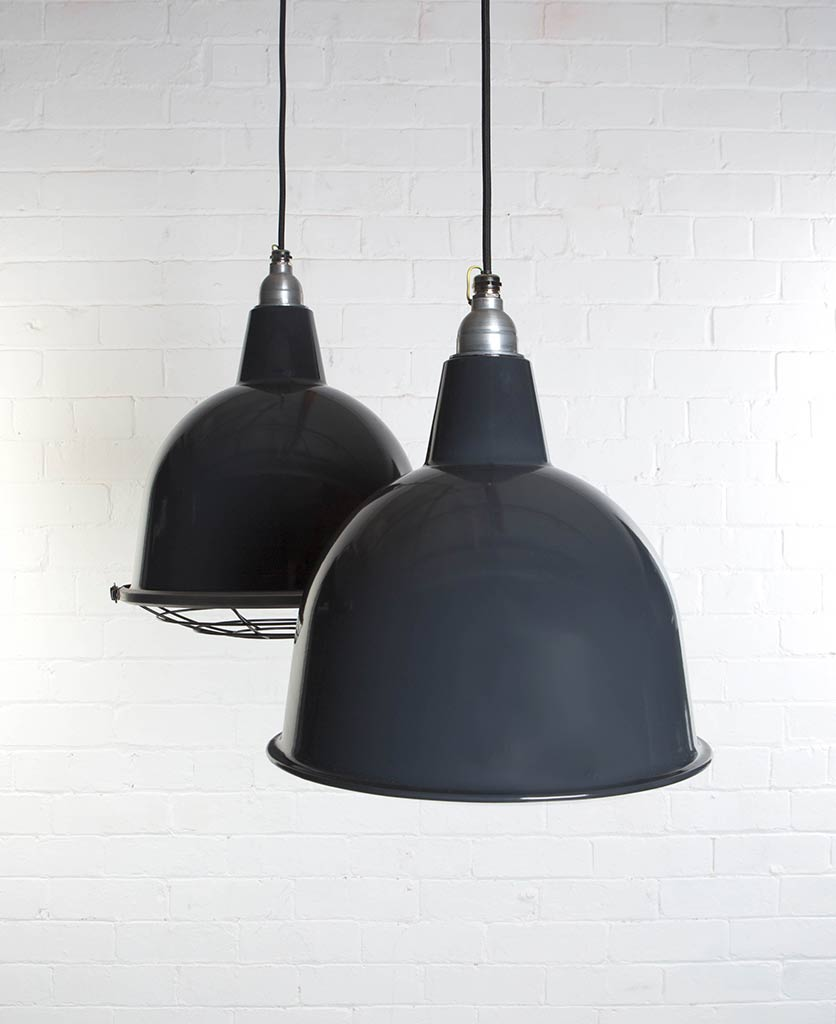 two grey stourton enamel pendant lights suspended from black fabric cable against painted white brick wall