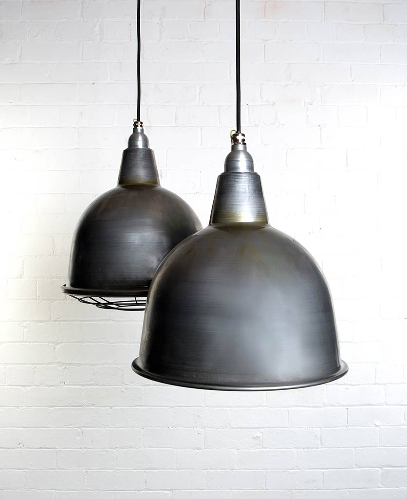 two raw steel stourton enamel pendant lights suspended from black fabric cable against painted white brick wall