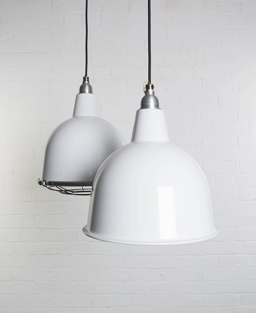 two white stourton enamel pendant lights suspended from black fabric cable against painted white brick wall