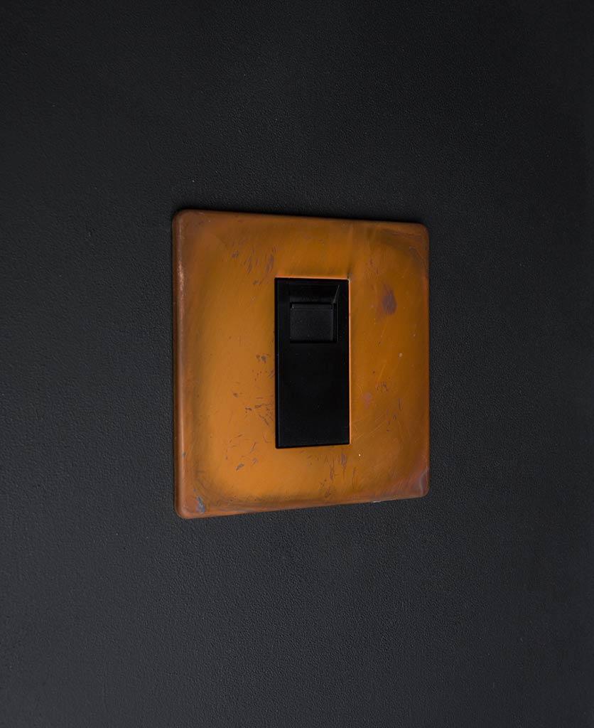 tarnished copper single data port with black insert against black background