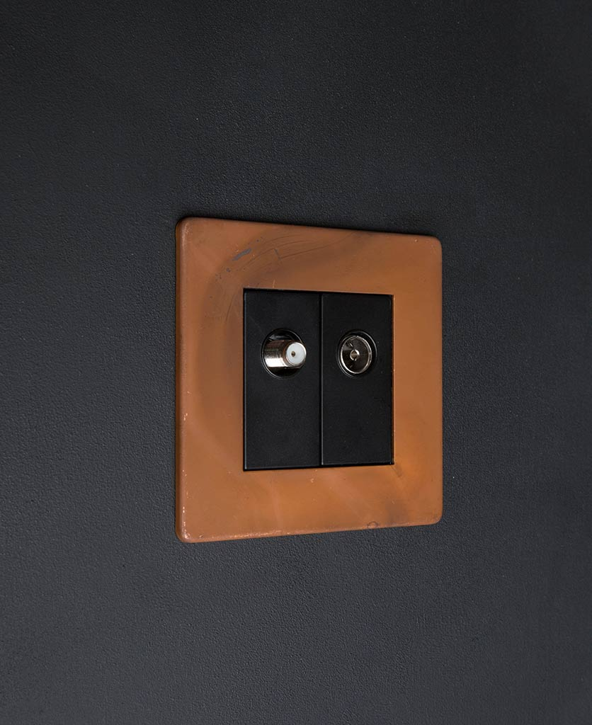tarnished copper double data port with black inserts against black background