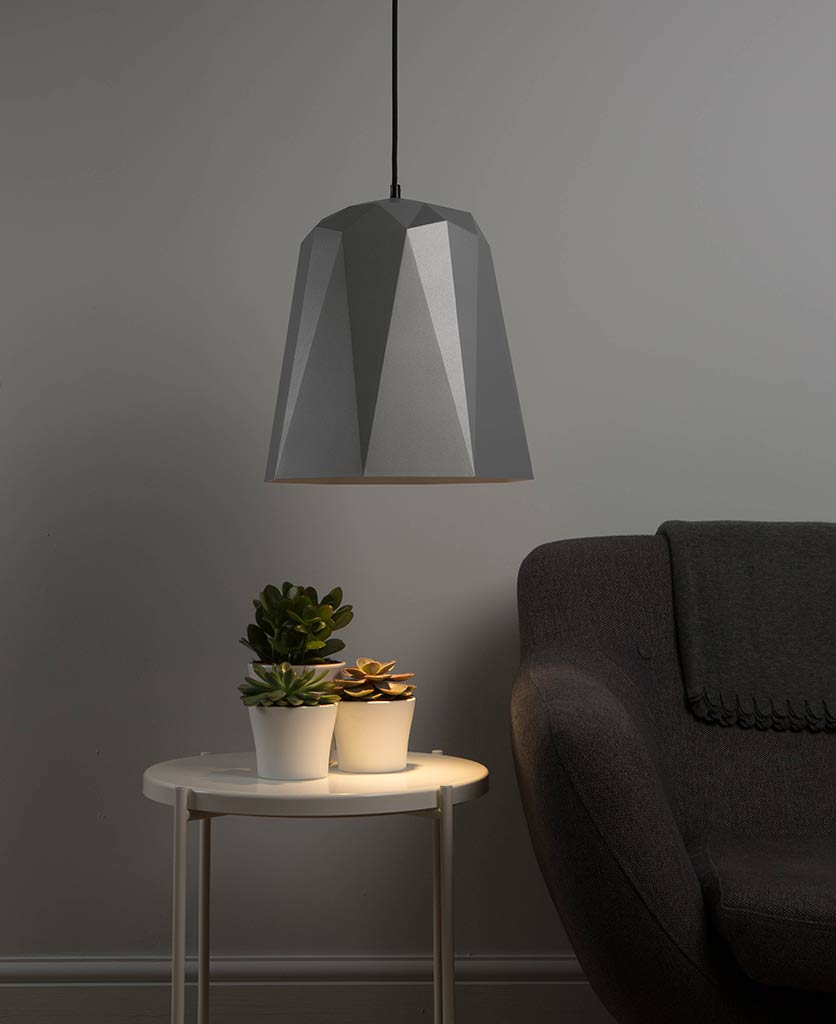 nagoya silver geometric ceiling light turned on suspended above a side table and grey sofa against a grey wall