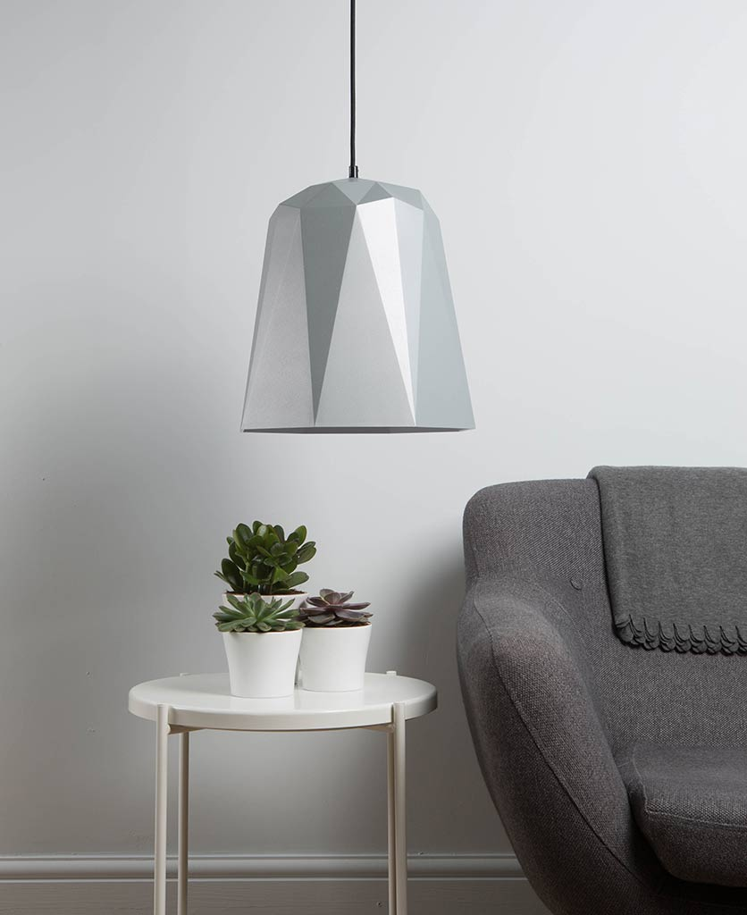 nagoya silver geometric ceiling light turned off suspended above a side table and grey sofa against a grey wall