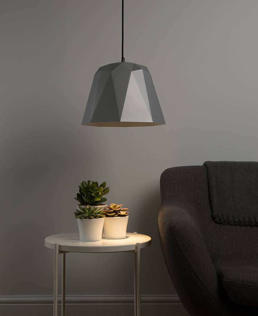 osaka silver geometric pendant light turned on suspended above a side table and grey sofa against a grey wall